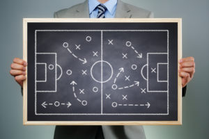 Business strategy businessman holding a blackboard planning team strategy on a chalk drawing of a soccer playing field